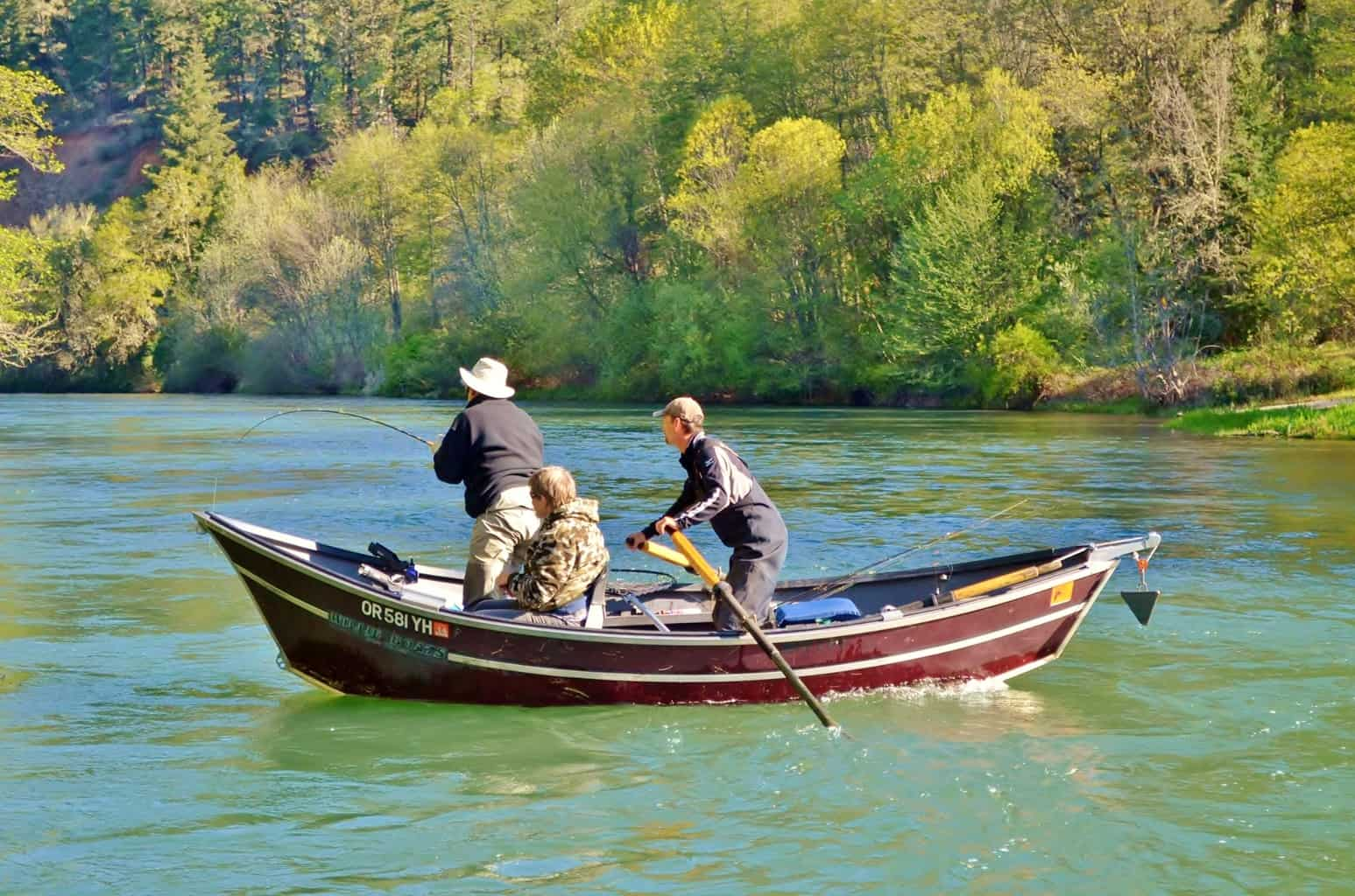 A drift boat with anglers fishing on the rogue river in southern Oregon.