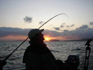 angler in silhouette trolling for salmon