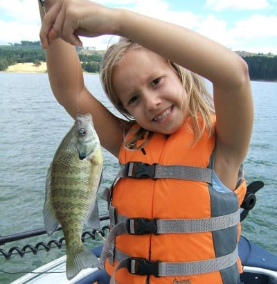 A girl holding a crappie she caught at one of the lakes near Portland we feature as being good to take kids fishing.
