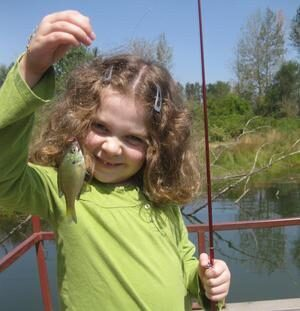 A girl with a small bluegill sunfish.