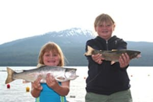 two young anglers hold up large trout they caught at diamond lake in oregon