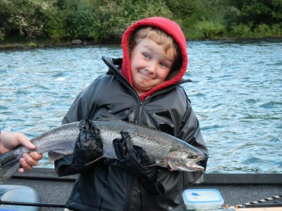 A grinning kid holding a big steelhead.