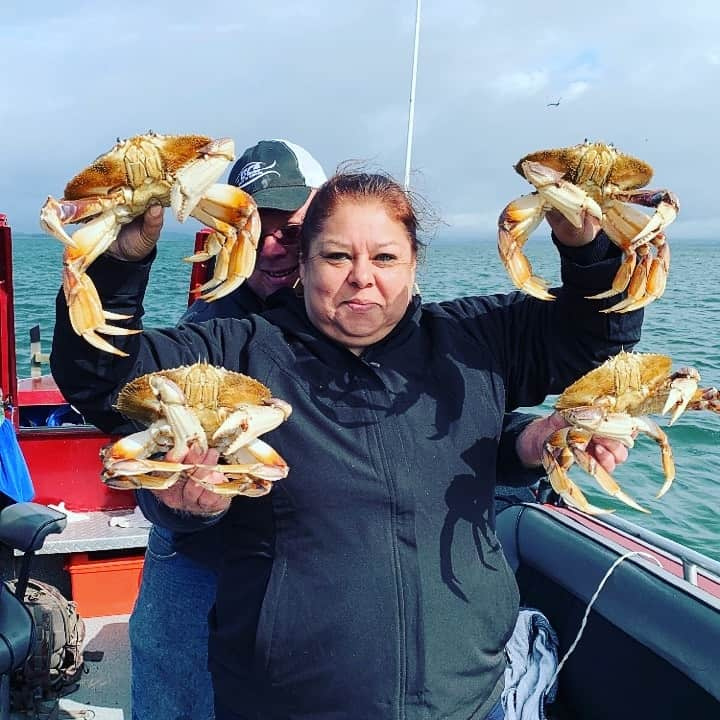 couple holding up dungeness crabs caught in tillamook bay in oregon