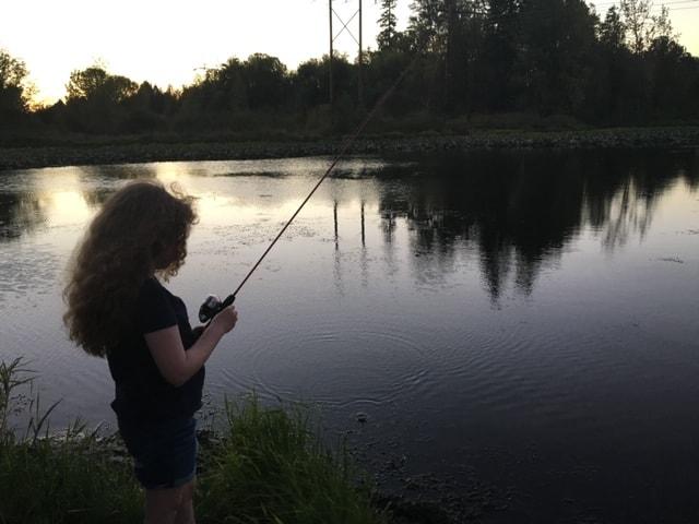 A girl fishing at Bethany Lake at dusk.
