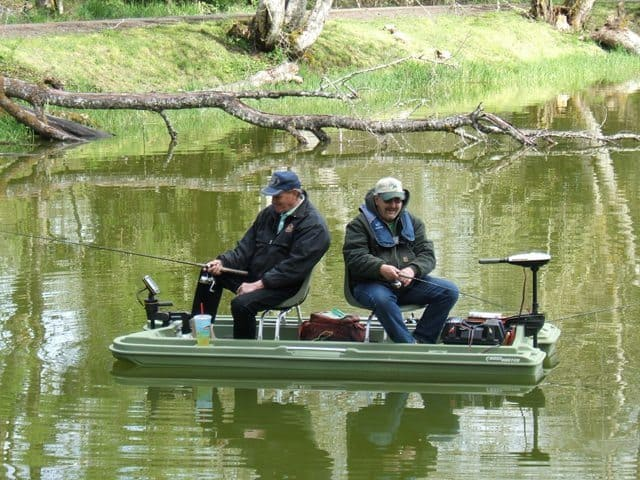 a couple of anglers fish from a small boat at vernonia lake
