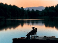 A silhouette of anglers with a scenic view of coffenbury lake on the background.