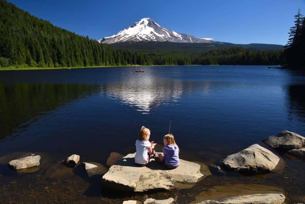 Kids sit on a big rock while fishing at trillium lake Oregon.