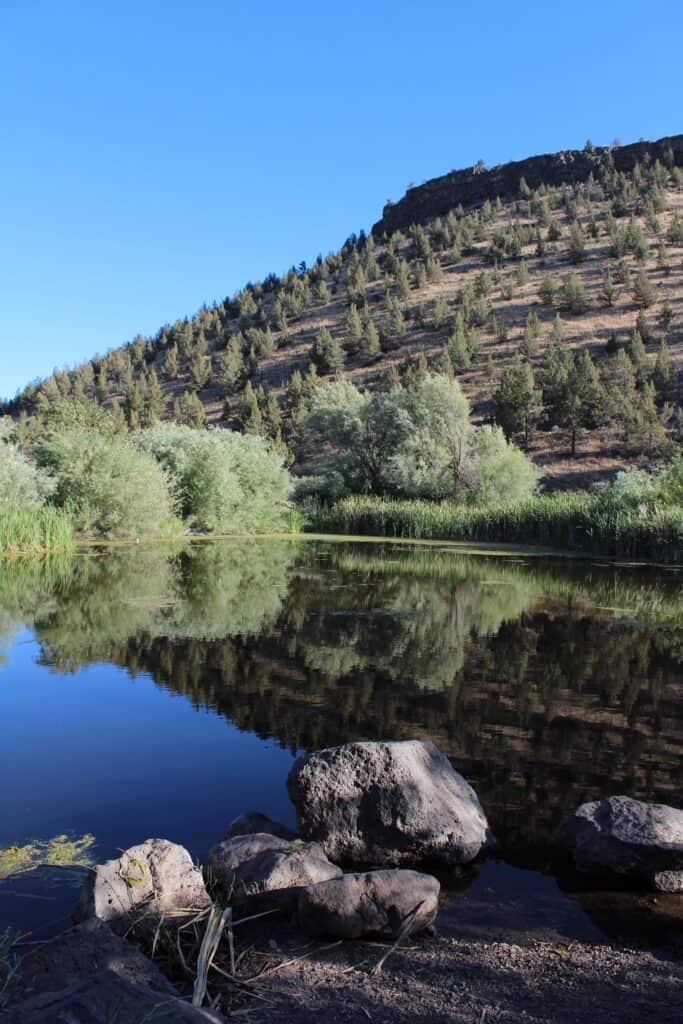 photo of hill reflecting in prineville youth pond