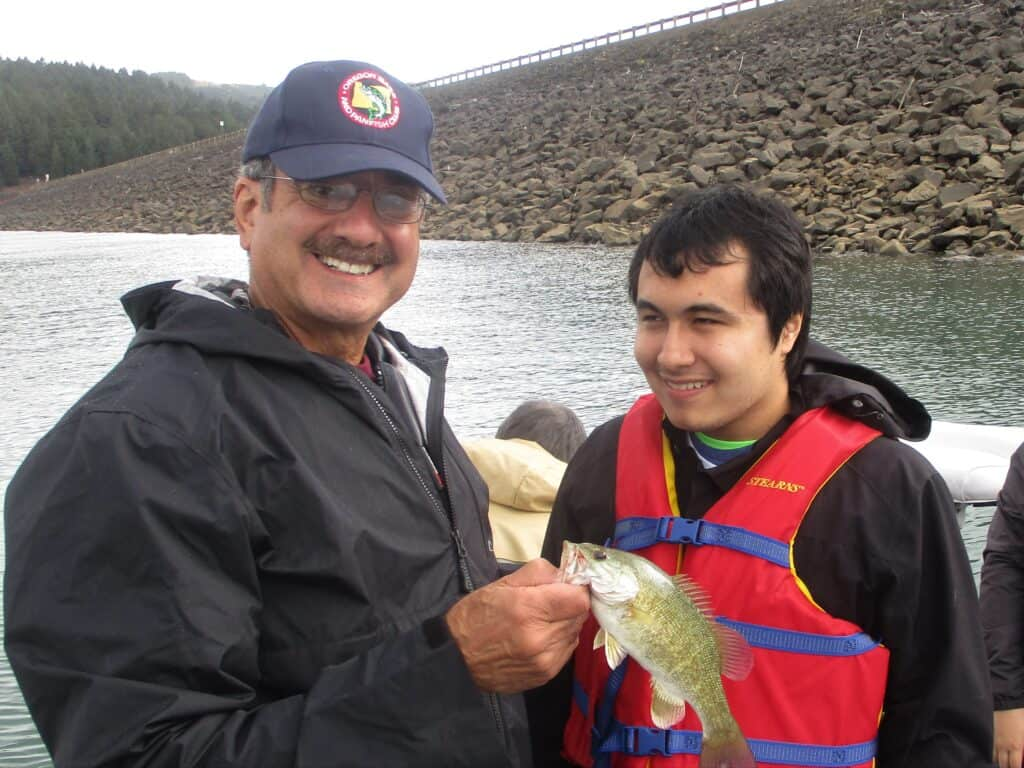 A boy smiles at a little smallmouth bass he caught with another angler's help.