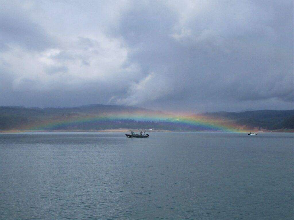 A rainbow curves over a fishing boat at Henry Hagg Lake in Oregon.