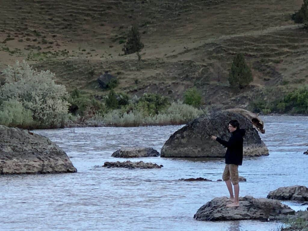 A barefoot boy casts for smallmouth bass during a multi-day float of the John Day River in Oregon.