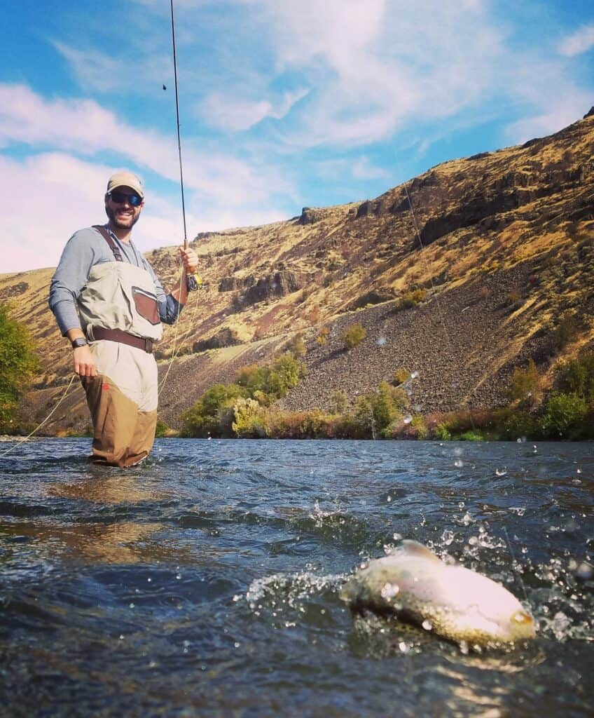 A trout splashes on the line while a fly fisherman smiles at his catch on the Yakima River