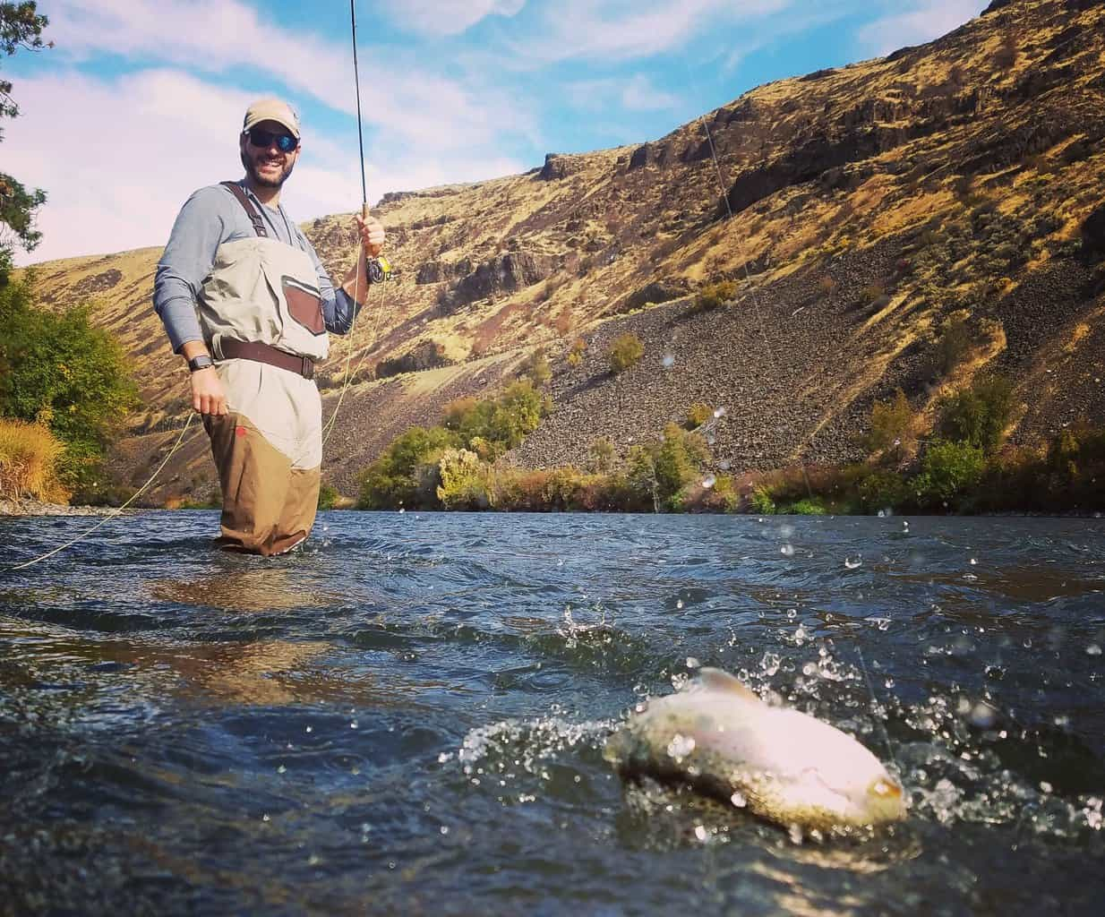 A fly angler landing a trout on the Yakima River.