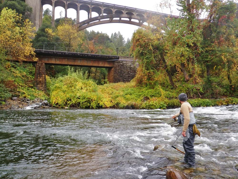 The upper Sacramento River flows under a scenic bridge with a fly angler casting into the river.