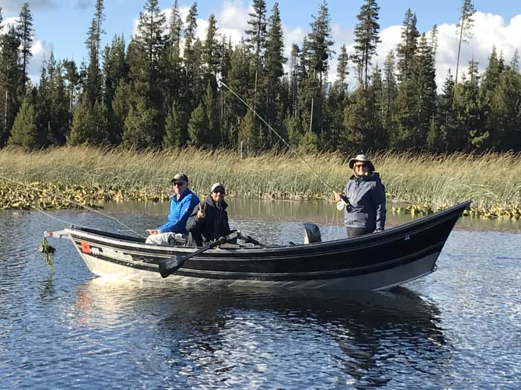 Anglers fly fishing from a drift boat on Hosmer Lake