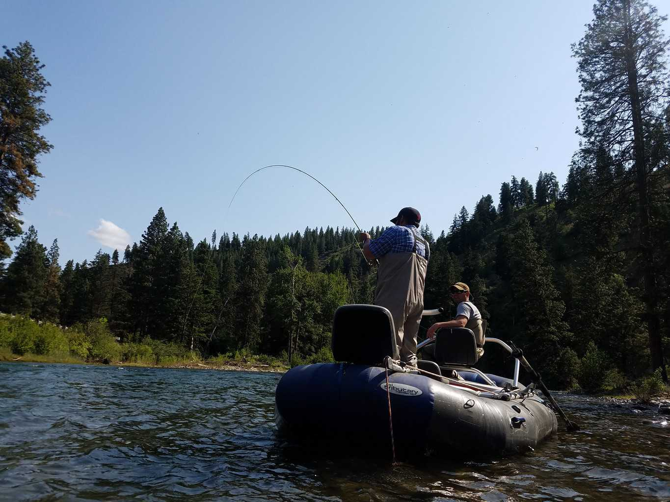 Anglers on a boat fly fishing and fighting a trout on the Naches River.