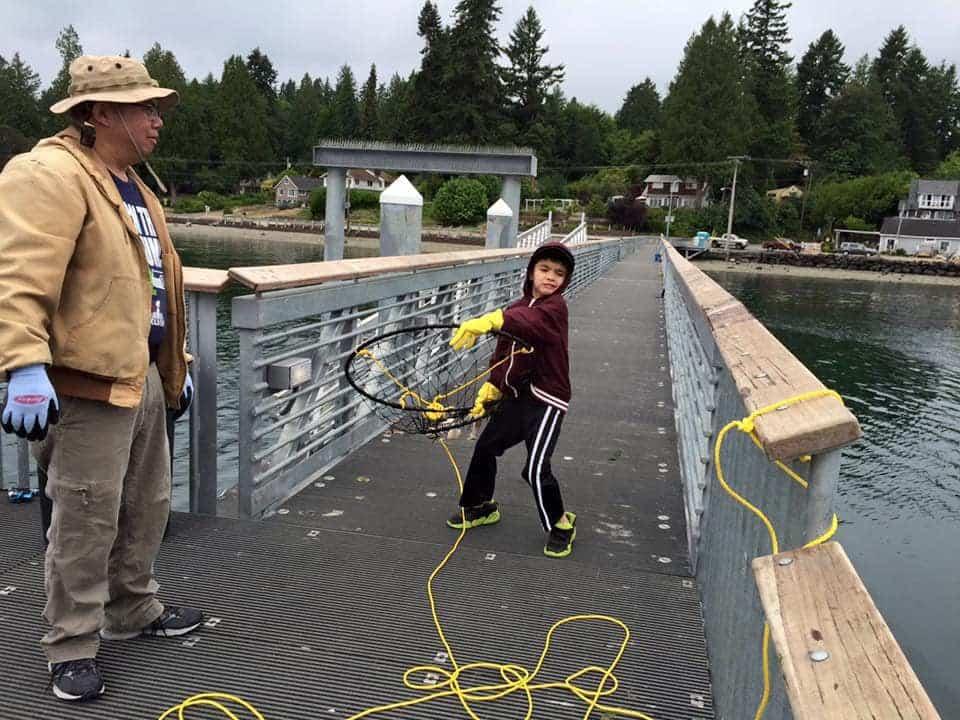 Boy crabbing from Harper Pier in Kitsap County, Washington