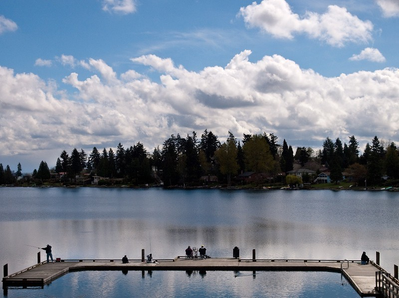 People fish from the pier at Angle Lake in SeaTac, Washington