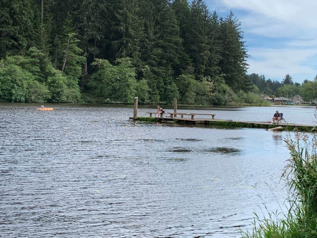 Anglers fishing from a pier at Cullaby Lake on the north Oregon Coast while a kayaker passes by.