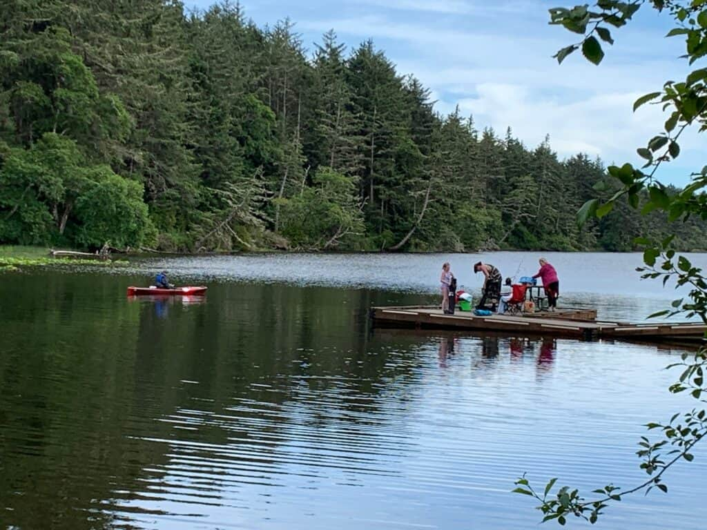 Dock anglers and a kayaker share a cove at the north end of Coffenbury Lake, where there is a small boat launch and lots of bank fishing access.