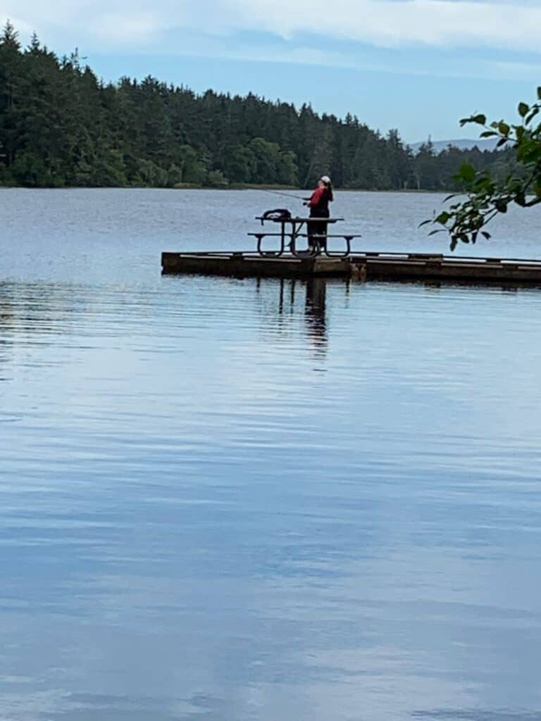 Angler fishing from a dock at Coffenbury Lake in Fort Stevens State Park