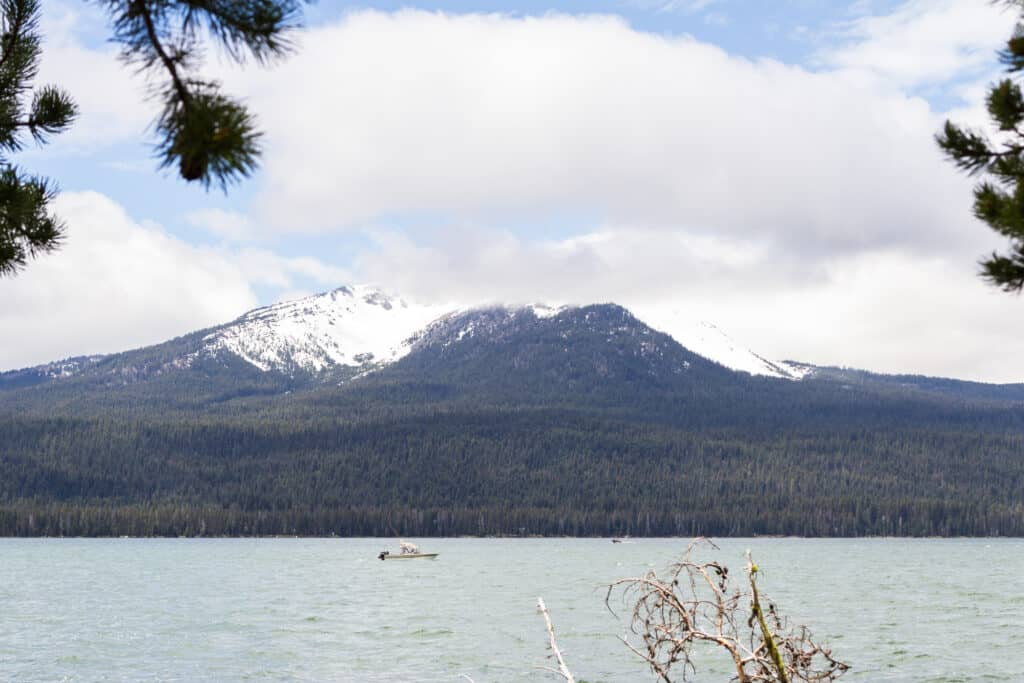 A boater fishes in Diamond Lake with Diamond Peak rising in the background.