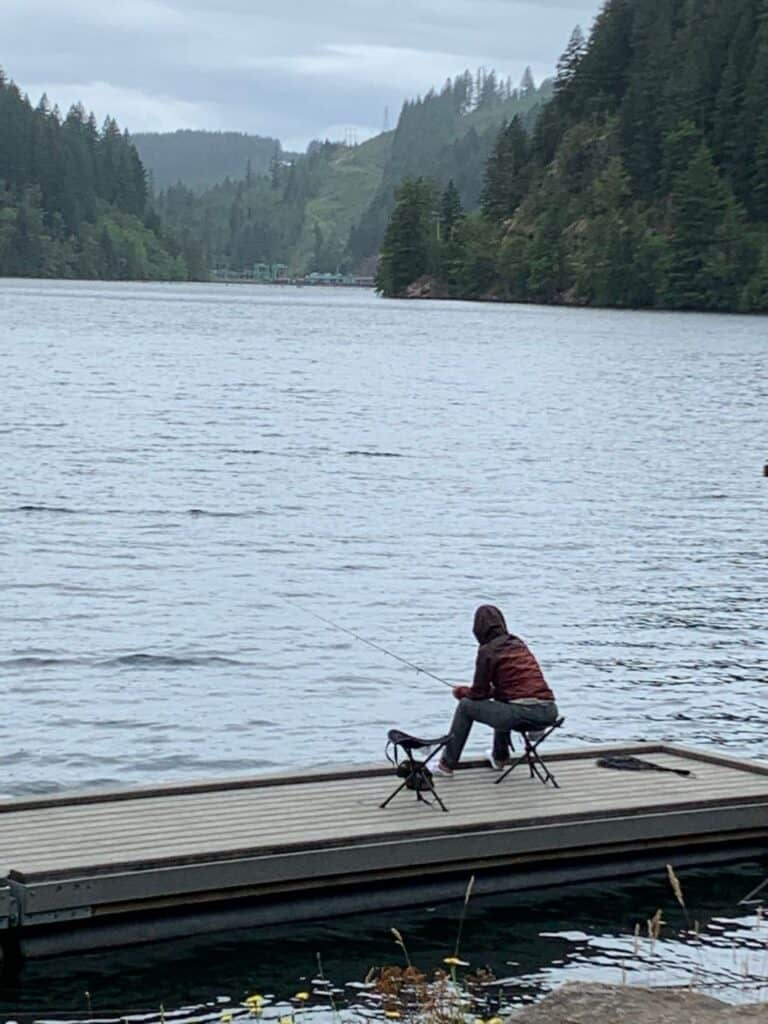 An angler fishes for trout from a fishing dock at the day use area on Faraday Road in the lower North Fork Reservoir.