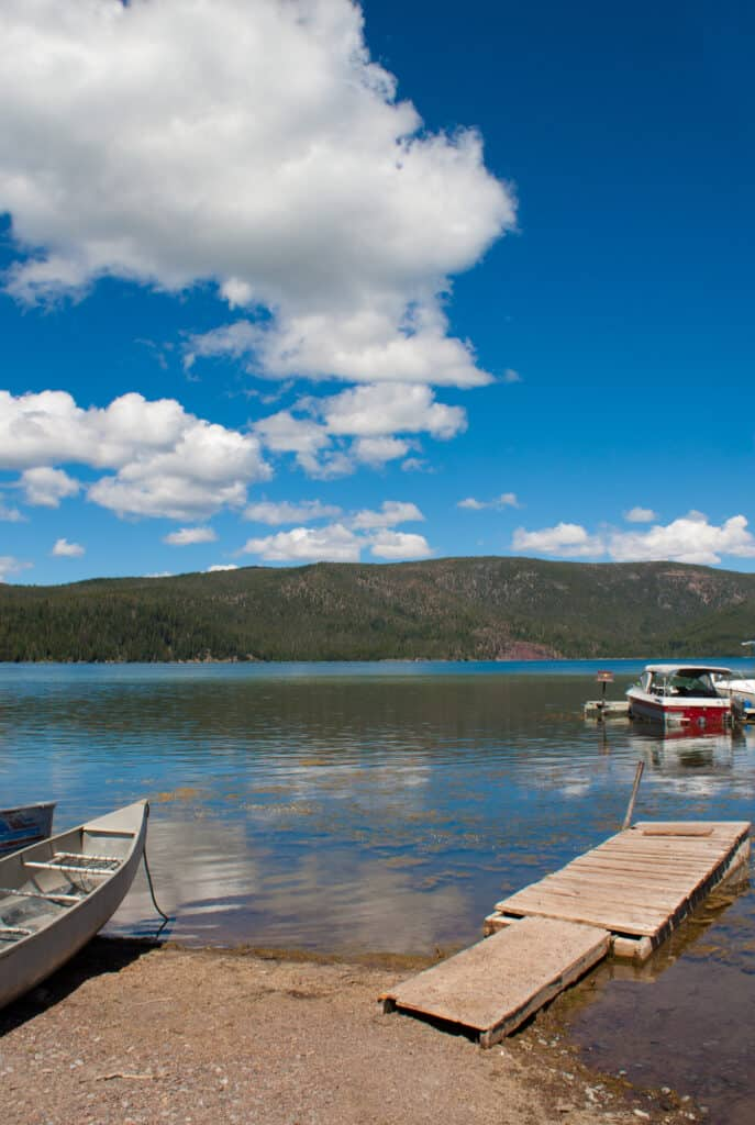 Paulina Lake dock with mountains and white clouds in background