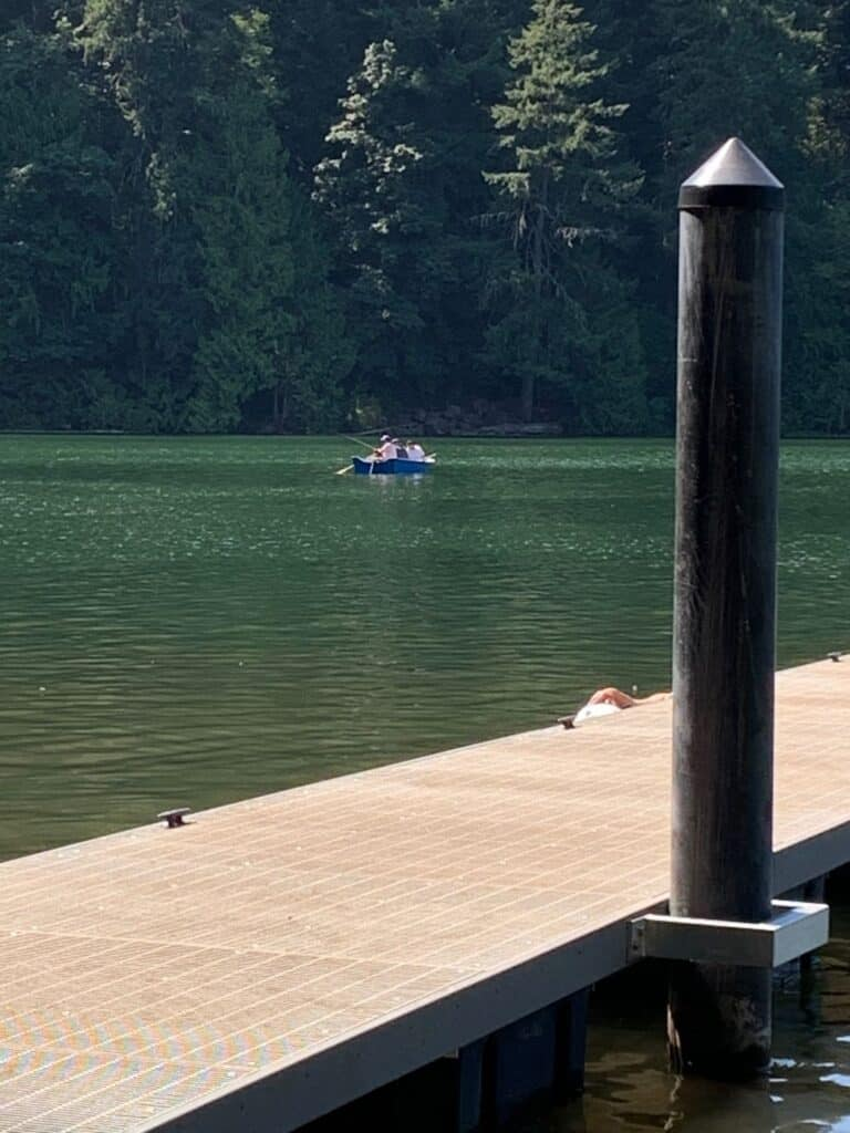 Anglers fish in a boat near the dock at battle ground lake