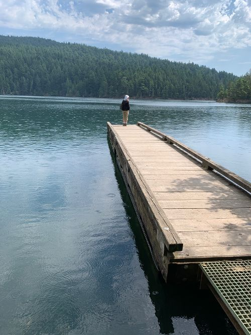 woman standing on a pier at mountain lake in moran state park