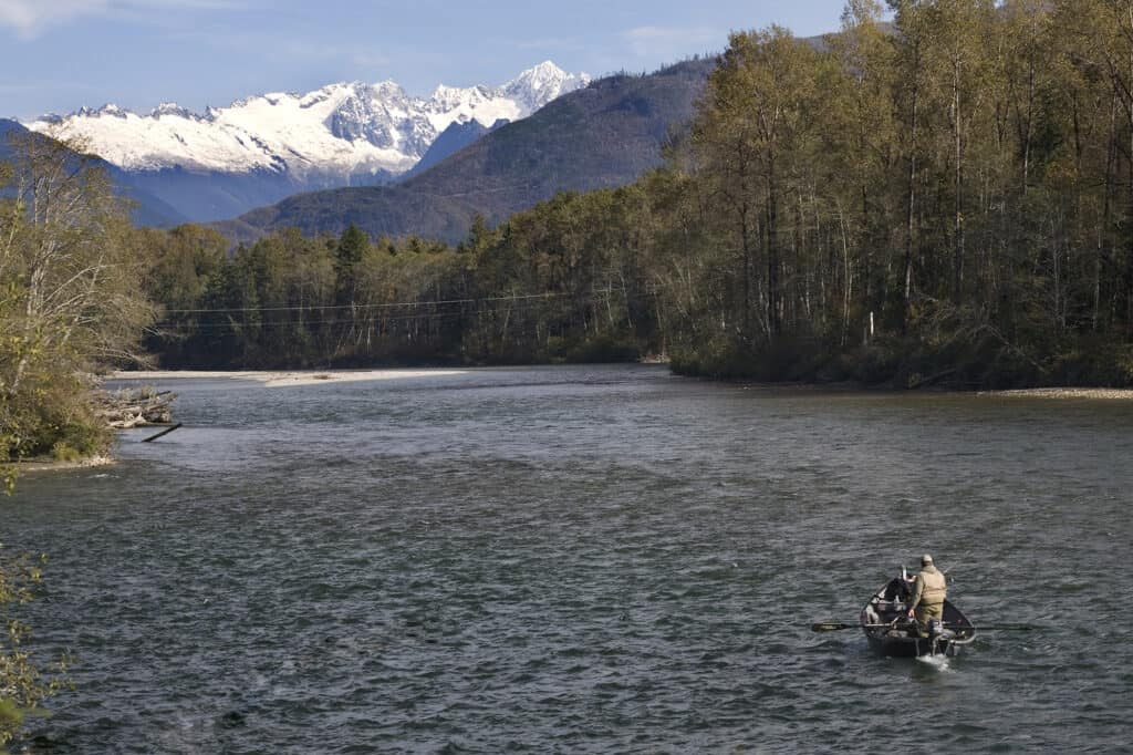 fishing boat on skagit river with snowy mountains in background