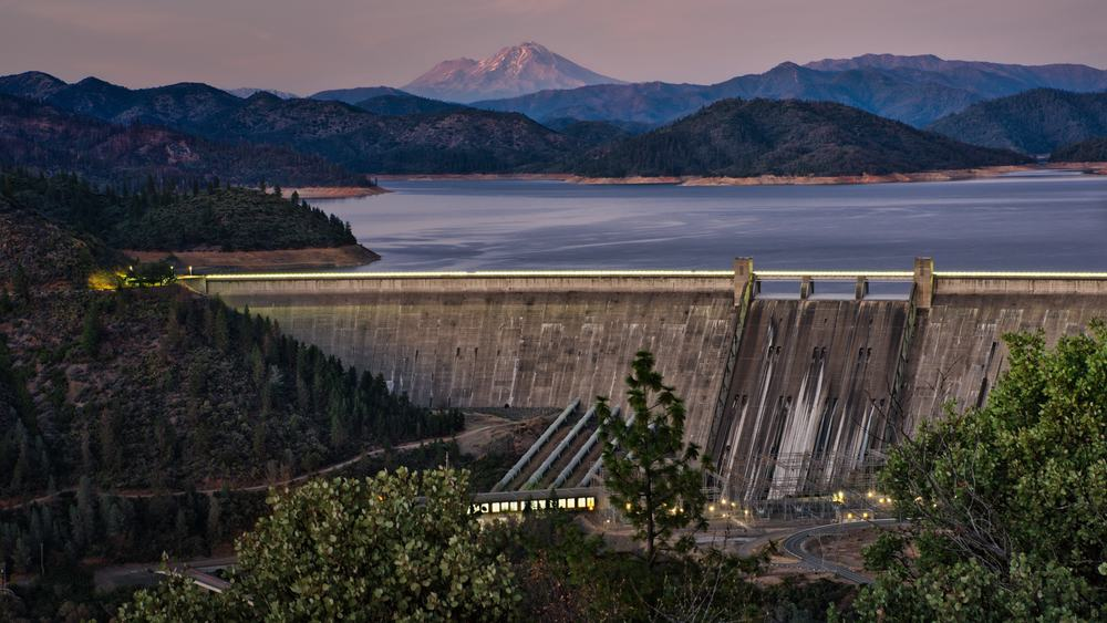 Shasta Lake scenic photo with the dam in the foreground and mount shasta in the distance.