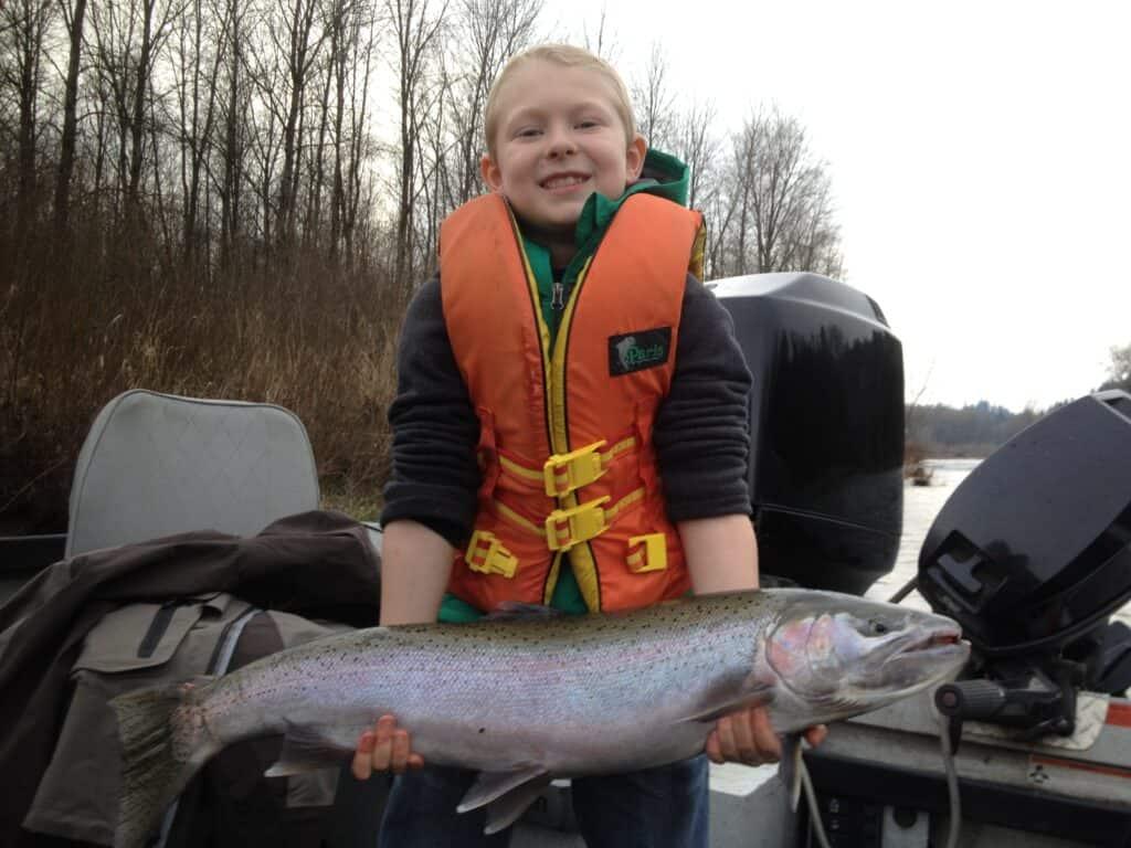 kid holding large clackamas river steelhead