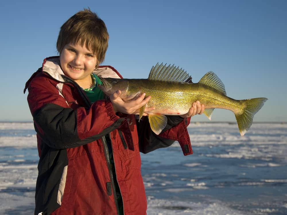 boy holding walleye in front of frozen lake