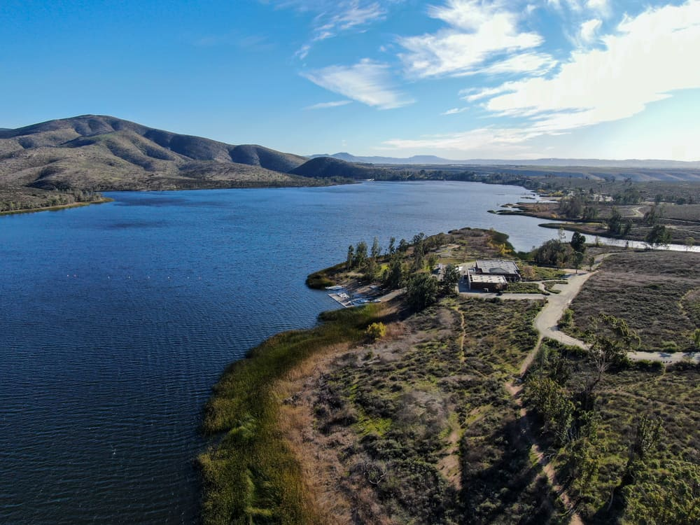 Aerial view of Otay Lake Reservoir with blue sky and mountain in the background near Chula Vista, California. Otay is a good bass fishing spot.