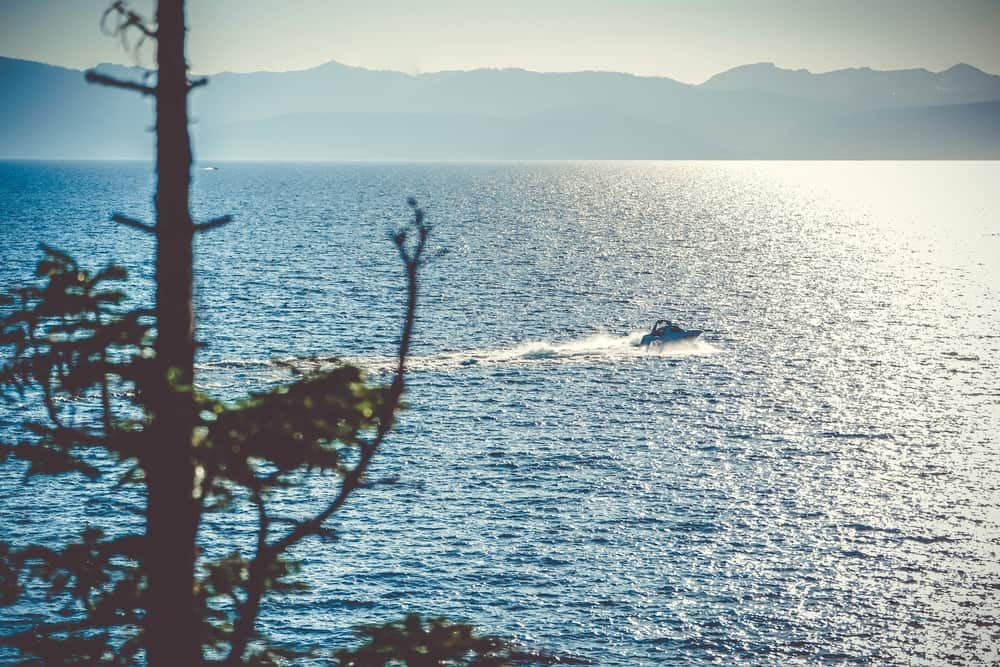 The sun glints off the water of Lake Tahoe while a boat powers across the surface.