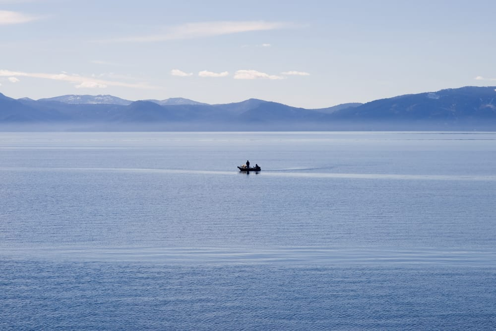 A fishing boat plies the waters of Lake Tahoe, known for kokanee salmon and trout fishing.