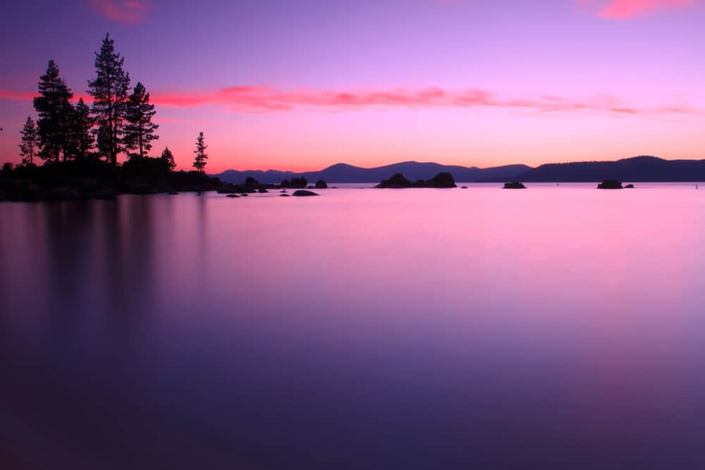 A scenic photo of Lake Tahoe with deep purples and pinks at sunset.