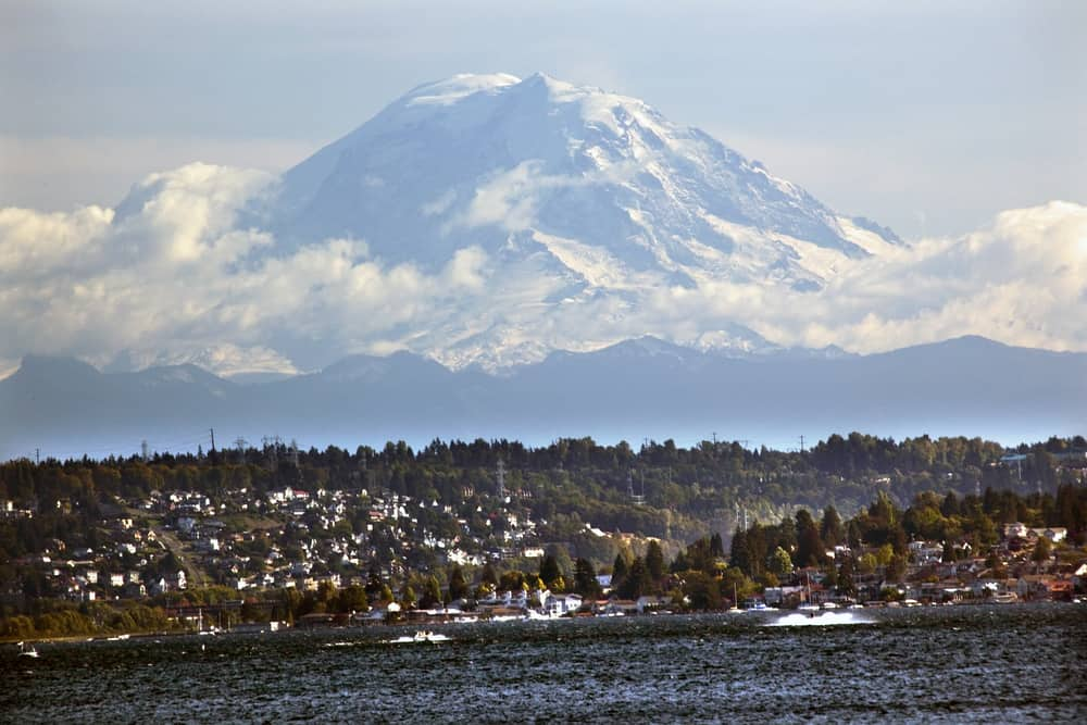 Mount Rainier looms large in the background with boats on Lake Washington in the foreground.