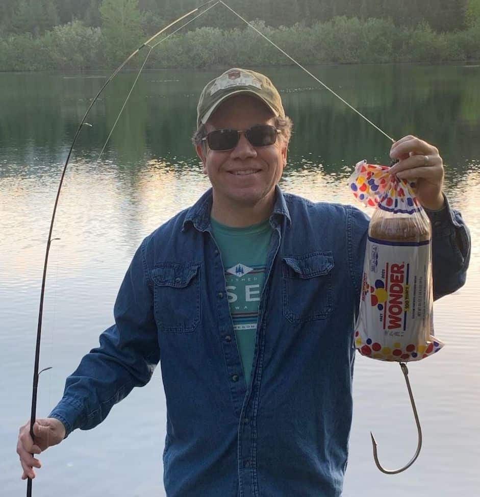 Angler holding a funny lure made with a real package of Wonder Bread and a giant shark hook.