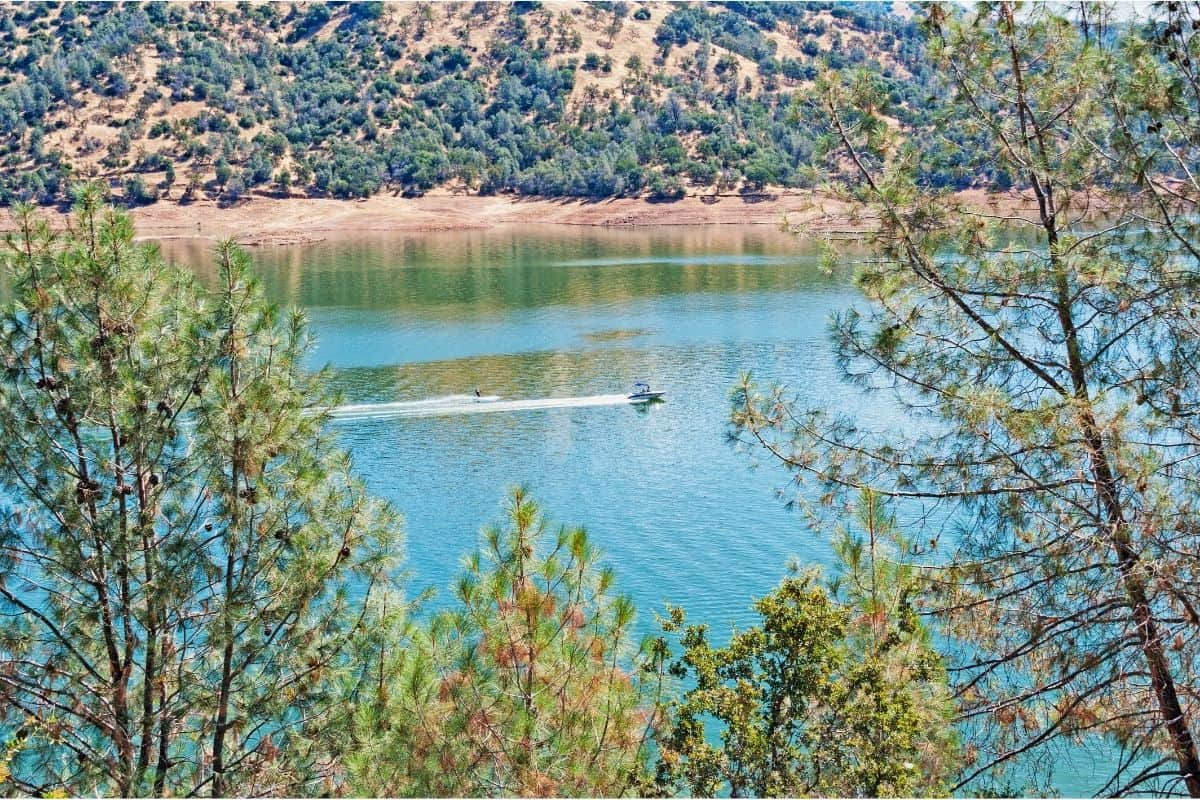A boat speeds across the surface of Don Pedro Lake.