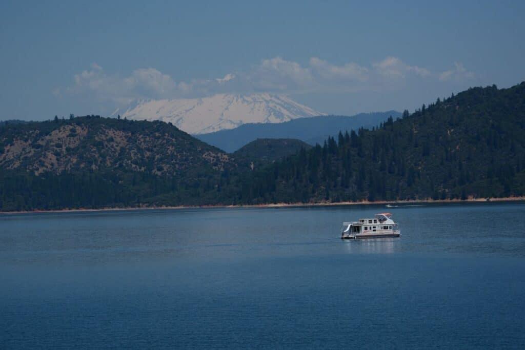 A houseboat motors slowly across Shasta Lake.