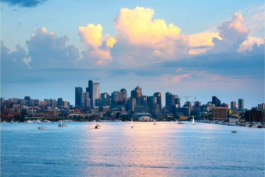 Clouds billow over boats on the surface of Lake Washington with Seattle as a backdrop.