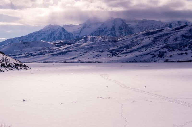 Frozen surface of Deer Creek Reservoir in Utah with ice fishing in distance.